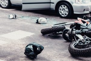 Helmet And Motorcycle Next To Broken Peaces Of A Car On The Street